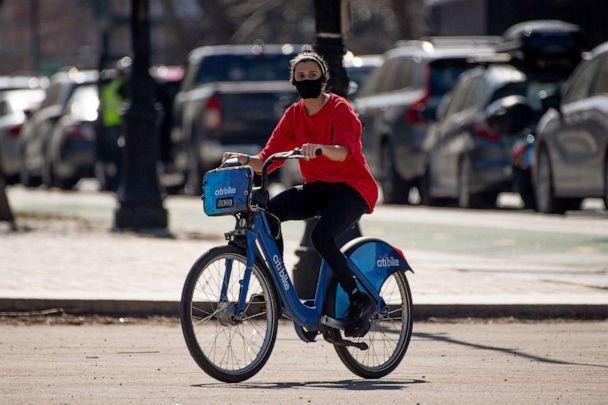 PHOTO: A woman rides a Citi Bike  while wearing a mask at Grand Army Plaza in Brooklyn, N.Y., March 9, 2021. (Roy Rochlin/Shutterstock)
