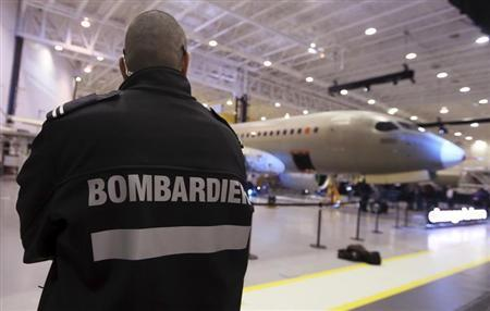 A security guard looks on as Bombardier unveils its CSeries aircraft at a news conference at its assembly facility in Mirabel, Quebec
