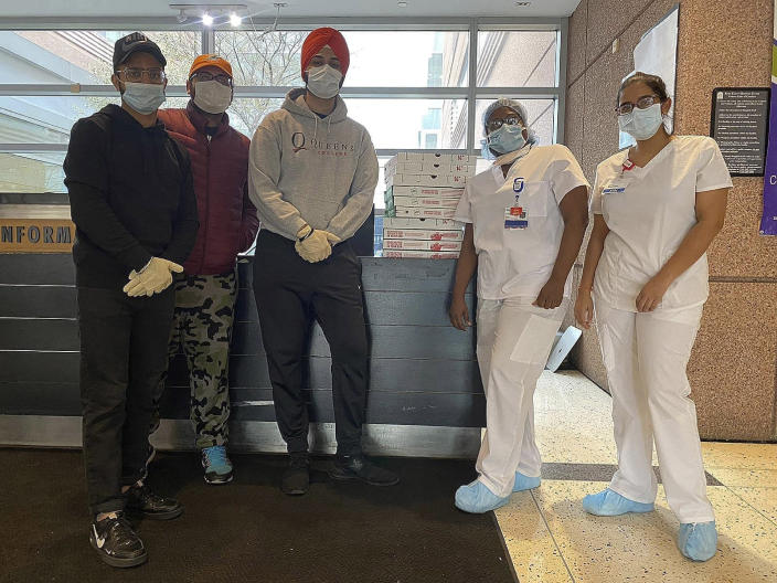 In this April 10, 2020, handout photo, Japneet Singh, center, and two other volunteers deliver pizza to health care workers at Kings County Hospital in the Brooklyn borough of New York. Singh estimates they have delivered 1,000 pizzas to essential workers since the end of March. (Courtesy of the New York Sikh Council via AP)