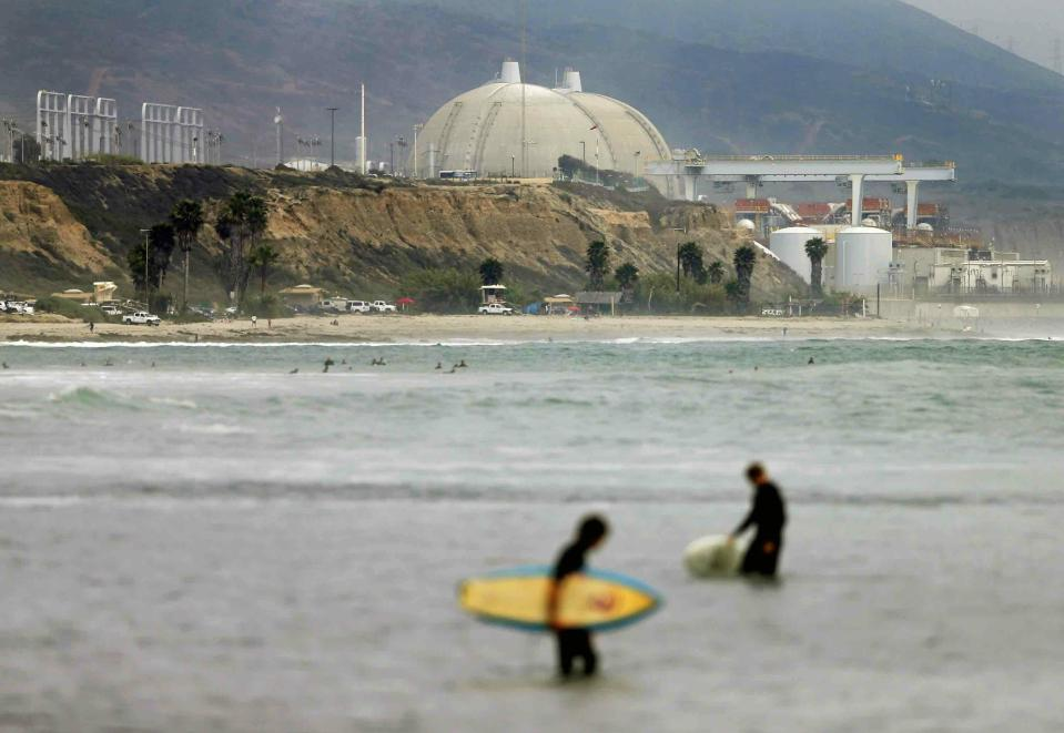 FILE - In this June 7, 2013 file photo surfers stand in water in front of the shuttered San Onofre Nuclear Generating Station in San Onofre, Calif. The Nuclear Regulatory Commission is fining Southern California Edison $116,000 for violations in its handling of nuclear canisters at the facility. The decision announced Monday, March 25, 2019, in an online town hall meeting involves the transfer of radioactive nuclear waste containers from cooling pools to safer bunkers. The Orange County Register reports Southern California Edison indicated it would accept the penalty. (AP Photo/Gregory Bull, File)