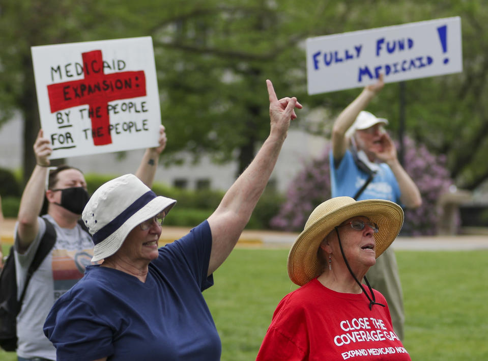 Maxine Horgan, left, and Barbara Nyden repeat the final chant of the Tuesday, April 27, 2021, Medicaid expansion rally at the Missouri State Capitol in Jefferson City. The Missouri Legislature is the latest statehouse fighting to undo voter-backed ballot measures. Missouri's GOP-led Senate this week voted against paying for voter-approved Medicaid expansion. (Liv Paggiarino/The Jefferson City News-Tribune via AP)