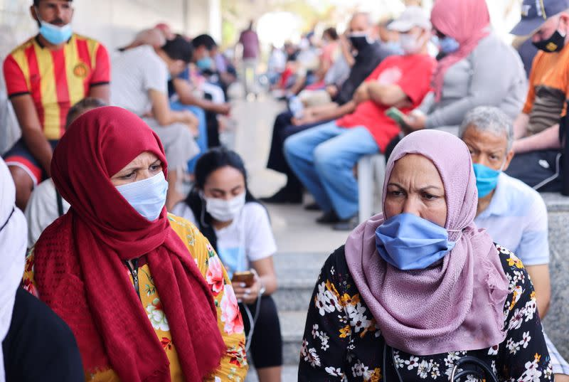 People wearing masks wait to receive the COVID-19 vaccine at a vaccination center in Tunis