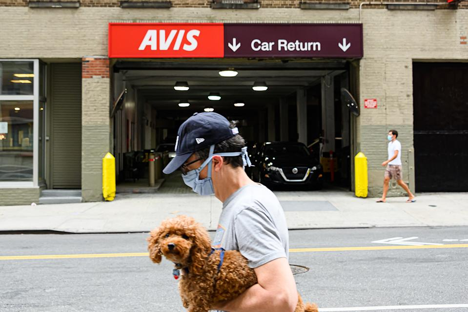 NEW YORK, NEW YORK - AUGUST 02: A person walks outside Avis car rental in Hell's Kitchen as the city continues Phase 4 of re-opening following restrictions imposed to slow the spread of coronavirus on August 2, 2020 in New York City. The fourth phase allows outdoor arts and entertainment, sporting events without fans and media production. (Photo by Noam Galai/Getty Images)