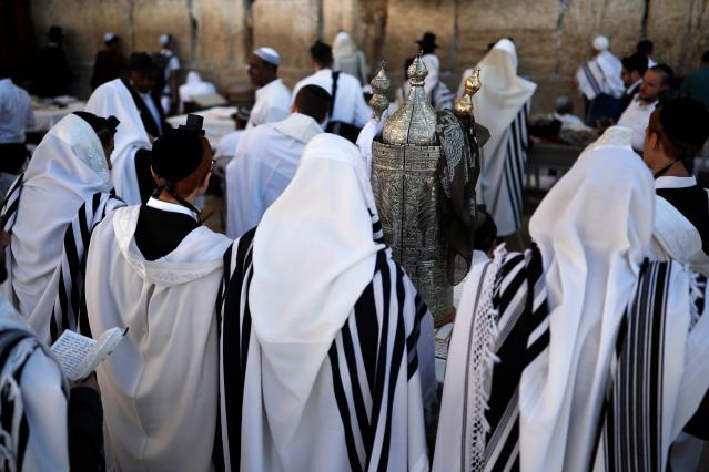 <p>Jewish men pray with a Torah scroll at the Western Wall in the Old City of Jerusalem on the eve of Yom Kippur also known as the Day of Atonement, the holiest day of the year in Judaism, on Sept. 28, 2017. (Photo: Thomas Coex/AFP/Getty Images) </p>