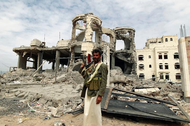 A Huthi militant poses next to a house that was destroyed by the Saudi-led coalition in Sanaa, on May 29, 2015 (AFP Photo/Mohammed Huwais)