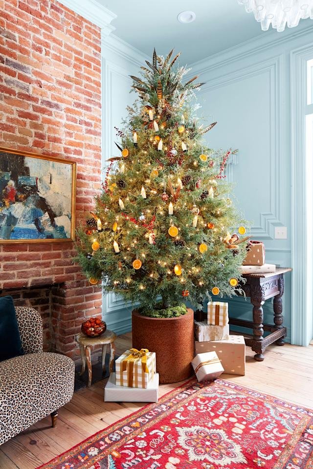 <p>A rust planter takes this gumdrop crypress to new heights. A strand of flameless candles adds an old-school effect while clove-studded oranges, dried-orange slices, and pinecones help the tree maintain an authentic look. </p>