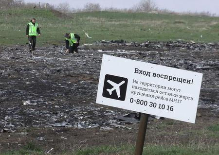 "Investigators work near a sign reading ""No entrance! There may be remains of the victims of flight MH17 crash at the territory"" at the site of the Malaysia Airlines Boeing 777 plane crash near the village of Hrabove (Grabovo) in Donetsk region, April 16, 2015. REUTERS/Igor Tkachenko"