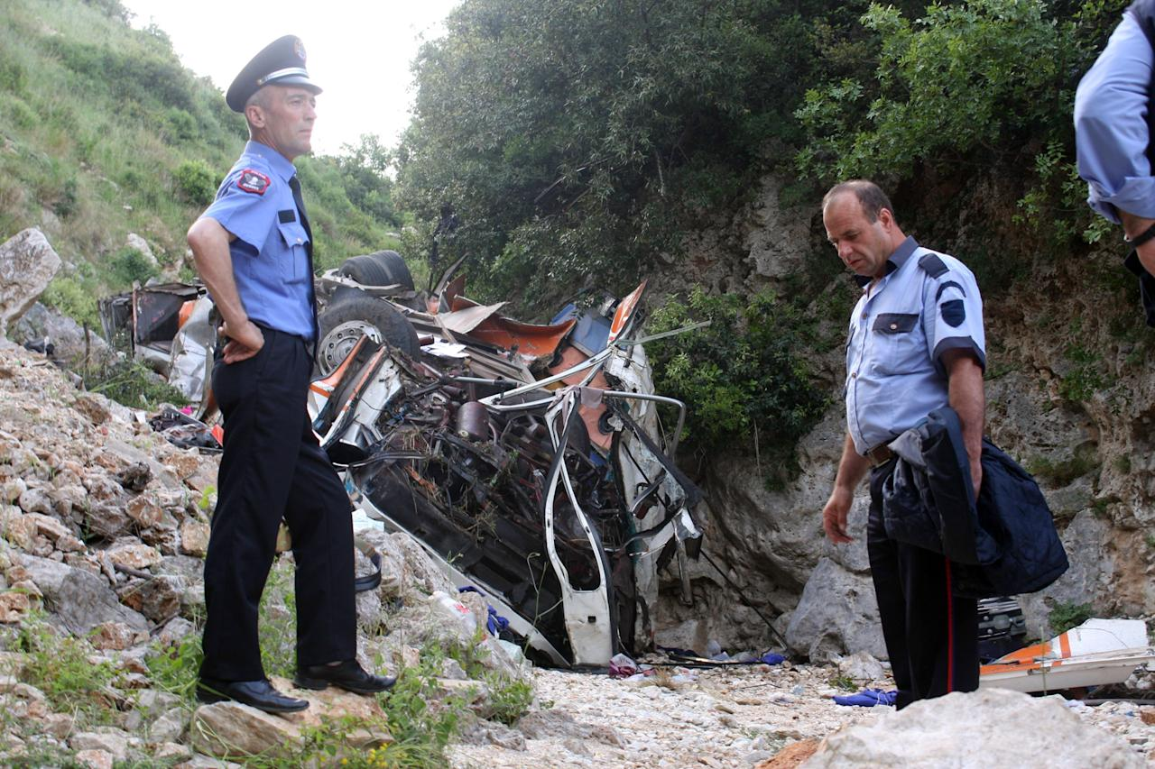 Rescue and security personnel attend the accident scene of the bus that was carrying university students at the bottom of a cliff near  Himare southern Albania on Monday, May 21, 2012  killing a number of people and injuring tens of others authorities said.  Local prefect Edmond Velcani said the bus driver was among the people killed.  The bus had been heading from the city of Elbasan to the southern city of Saranda. Police spokeswoman Klejda Plangarica said the bus fell some 80 meters (yards) off the road in Qafa e Vishes near the town of Himare, 137 miles (220 kilometers) south of the capital, Tirana, on Monday afternoon. (AP Photo)