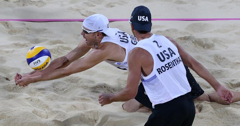 Sean Rosenthal, right, of US looks on as his teammate Jake Gibb, left, dives for a ball during the Beach Volleyball match against Poland at the 2012 Summer Olympics, Monday, July 30, 2012, in London. (AP Photo/Petr David Josek)