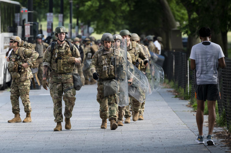Military troops disembark from tour buses and deploy inside the security perimeter at the White House. (Bill Clark/CQ-Roll Call Inc. via Getty Images)
