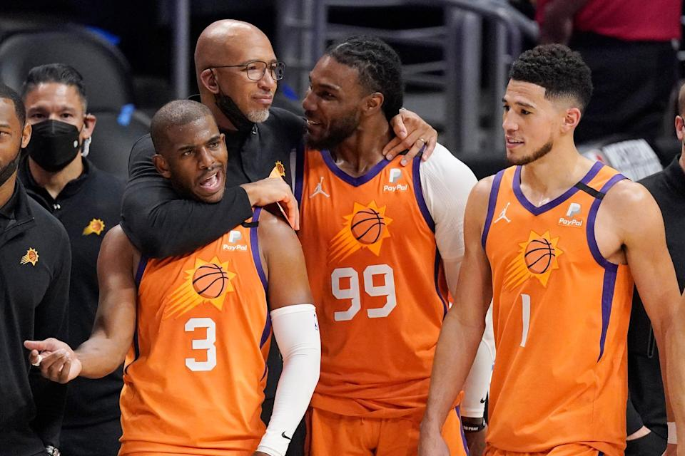 Suns coach Monty Williams (second from left) celebrates his team's Western Conference title with Chris Paul (3), Jae Crowder (99) and Devin Booker.