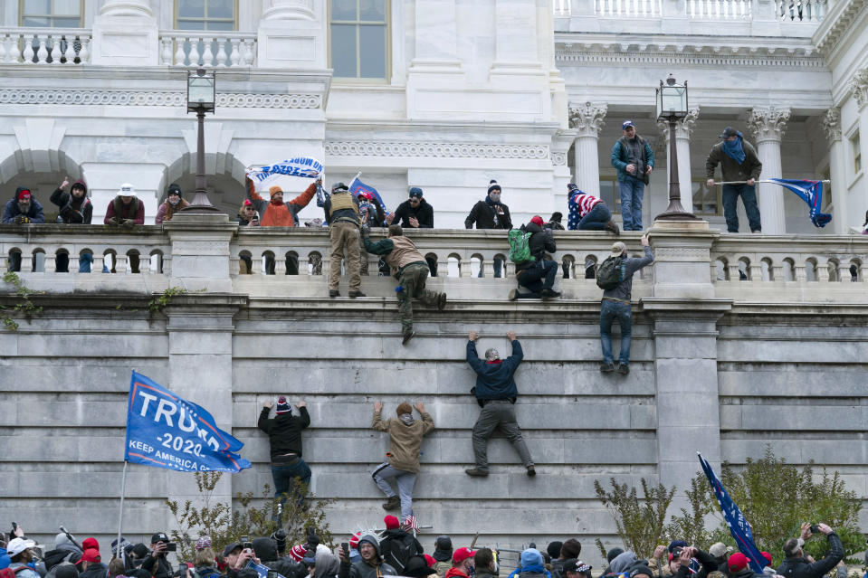 FILE - In this Jan. 6, 2021, file photo violent insurrectionists loyal to President Donald Trump climb the west wall of the the U.S. Capitol in Washington. A month ago, the U.S. Capitol was besieged by Trump supporters angry about the former president's loss. While lawmakers inside voted to affirm President Joe Biden's win, they marched to the building and broke inside. (AP Photo/Jose Luis Magana, File)