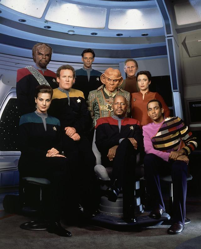 <p>Setting a series aboard a shared space station, as opposed to a Federation vessel, allowed <em>Deep Space Nine </em>to expand on the franchise's character and costume profile. The darker Starfleet jumpsuits reflect the show's own darker, more complex storytelling, and the prominent ppresenceof Bajoran and Ferengi fashions in the frame speaks to the mix of cultures that inhabit this deep space outpost.<br><br>(Photo: CBS) </p>