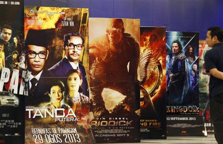 "A movie-goer looks at the ""Tanda Putera"" poster among other movie posters at a cinema in Putrajaya"