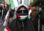 A Muslim woman wears a face mask with the colors of Palestinian flag during a rally condemning Israeli attacks on the Palestinians in Jakarta, Indonesia, Tuesday, May 18, 2021. (AP Photo/Dita Alangkara)