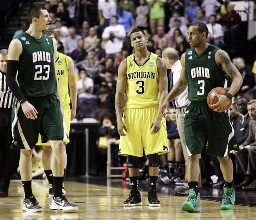 Michigan guard Trey Burke, center, looks on as Ohio guard Walter Offutt, right, is congratulated by Ivo Baltic (23) after Offutt drew a foul against Michigan in the final seconds of a second-round NCAA college basketball tournament game on Friday, March 16, 2012, in Nashville, Tenn. The resulting free throws by Offutt sealed a 65-60 win for Ohio. (AP Photo/Mark Humphrey)