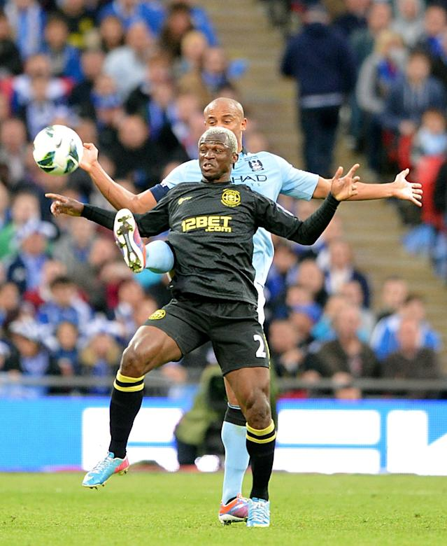 Wigan Athletic's Arouna Kone (front) and Manchester City's Vincent Kompany battle for the ball