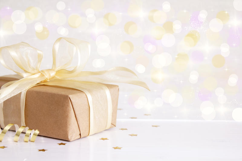 Gift box tied with a gold ribbon, on a defocused background.
