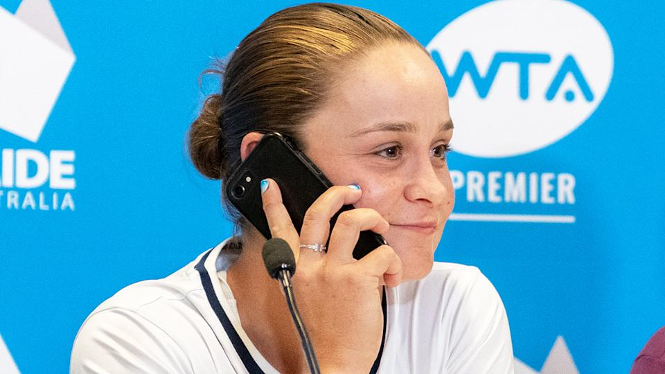 Ash Barty, pictured as she answers a journalist's phone during a press conference ahead of the Adelaide International.