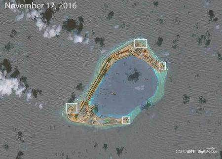 A satellite image shows what CSIS Asia Maritime Transparency Initiative says appears to be anti-aircraft guns and what are likely to be close-in weapons systems (CIWS) on the artificial island Subi Reef in the South China Sea