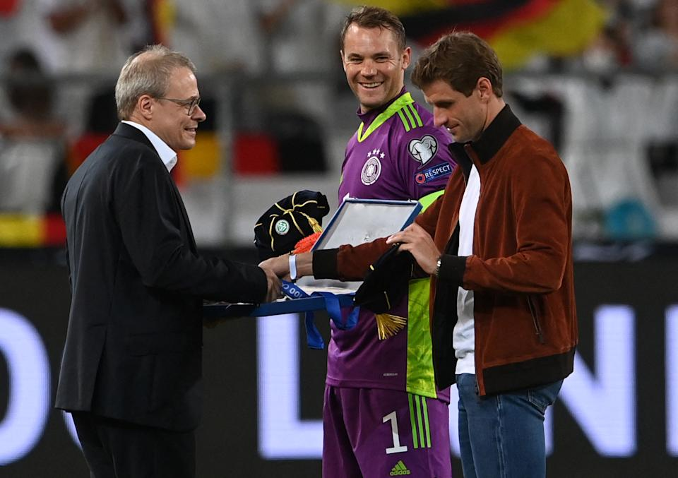 Germany's goalkeeper Manuel Neuer (C) and Germany's forward Thomas Mueller (R) receive a cap for 100 international appearances ahead the FIFA World Cup Qatar 2022 qualification Group J football match between Germany and Armenia, in Stuttgart, on September 5, 2021.