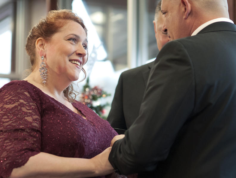 Bride Valerie Sneade places the ring on groom Jason Roy's finger during their wedding ceremony at the Dunkin' Donuts on Friday, Dec. 27, 2019 in Worcester, Mass.  The couple reunited for their wedding vows at the Dunkin' Donuts where their young love splintered nearly thirty years ago. Except for a couple of chance encounters, Sneade and Roy mostly didn't see each other for 25 years after a conversation about their future at the same donut shop in 1992 led the young couple to slowly cut ties. Sneade and Roy blame misunderstandings at the time and words that didn't come out right.  (Rick Cinclair/Worcester Telegram & Gazette via AP)