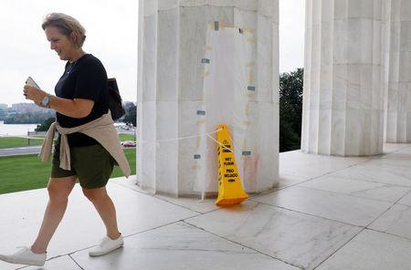 A tourist walks past a papered-over column where a vandal scrawled obscene graffiti in spray paint on the Lincoln Memorial in Washington, U.S. August 15, 2017.  REUTERS/Jonathan Ernst