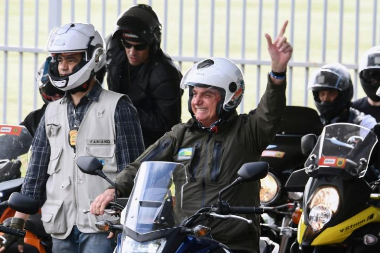 Brazil's President Jair Bolsonaro waves to supporters as he rides a motorcycle leading a caravan of more than 1000 bikers May 9, 2021