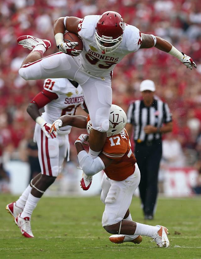 DALLAS, TX - OCTOBER 12: Trey Millard #33 of the Oklahoma Sooners carries the ball against Adrian Phillips #17 of the Texas Longhorns in the first quarter at the Cotton Bowl on October 12, 2013 in Dallas, Texas. (Photo by Tom Pennington/Getty Images)