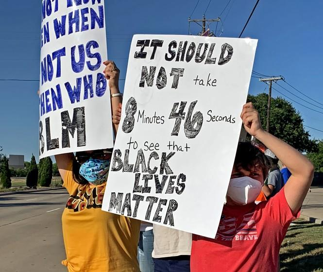 Mike Sexton's wife and son, Lee Anne, left, and Tyler, 11, during a unity rally outside Grapevine, Texas, that Sexton organized to protest excessive use of force and racial bias in policing. (Courtesy of Mike Sexton)