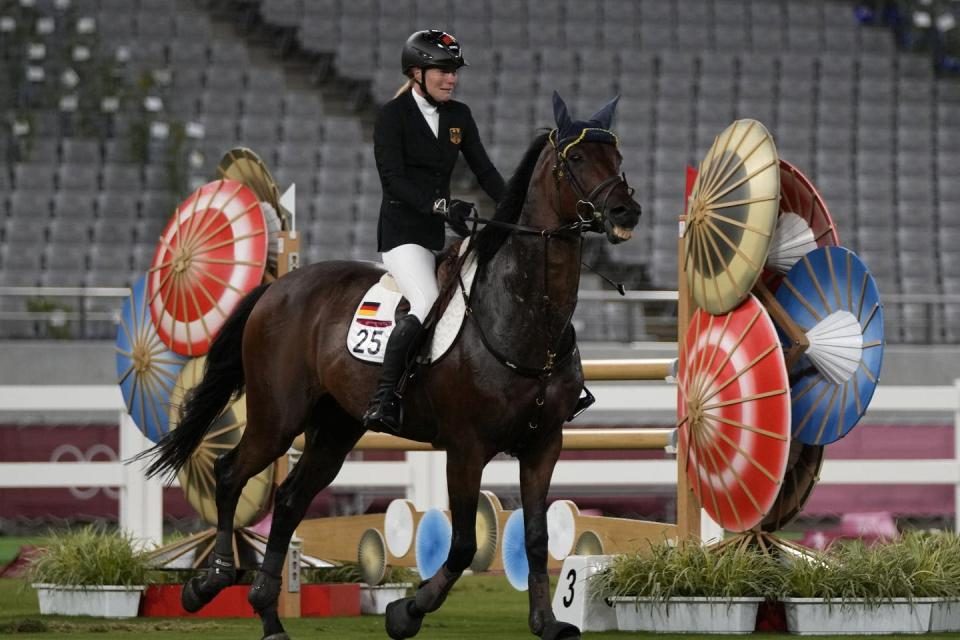 """<span class=""""caption"""">Annika Schleu of Germany cries when Saint Boy, the horse she was assigned to ride, wouldn't co-operate in the equestrian portion of the modern pentathlon at the Tokyo Summer Olympics. </span> <span class=""""attribution""""><span class=""""source"""">(AP Photo/Hassan Ammar) </span></span>"""