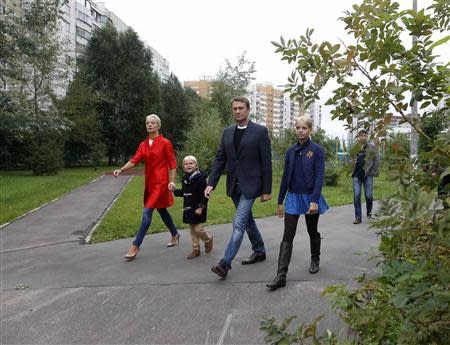 Russian opposition leader Alexei Navalny (2nd R), accompanied by his wife Yulia (L) and children Dasha and Zakhar (2nd L), walks to a polling station in Moscow September 8, 2013. REUTERS/Maxim Shemetov