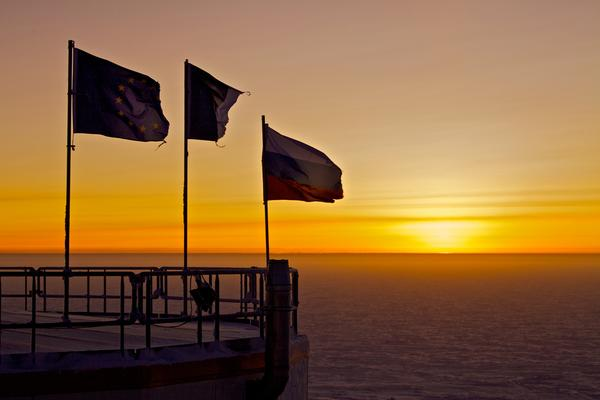 On Aug. 12, the first sunrise at Concordia Research Station reveals flags tattered by the brutal conditions of Antarctica's dark winter months.
