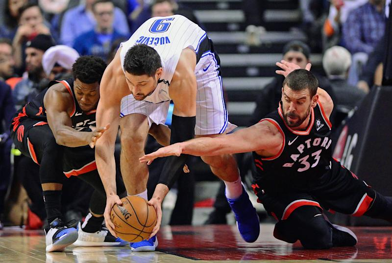 Orlando Magic center Nikola Vucevic (9) tries to protect the ball from Toronto Raptors guard Kyle Lowry, left, and center Marc Gasol right, during the first half of an NBA basketball game in Toronto on Monday, April 1, 2019. (Frank Gunn/The Canadian Press via AP)