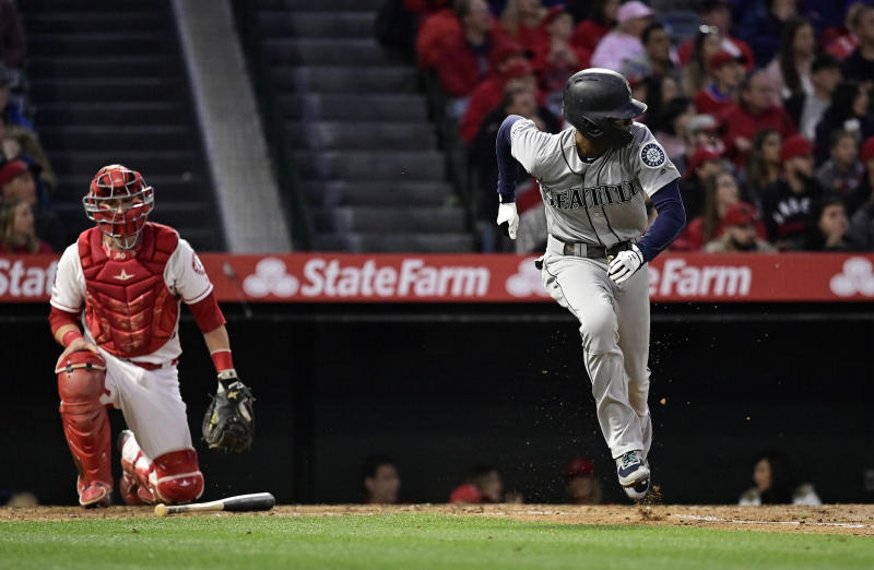 Seattle Mariners' Dee Gordon, right, runs to first as he hits an RBI single while Los Angeles Angels catcher Jonathan Lucroy watches during the fourth inning of a baseball game Saturday, April 20, 2019, in Anaheim, Calif. (AP Photo/Mark J. Terrill)