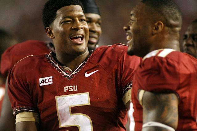 Florida State quarterback Jameis Winston (5) chats with defensive end Chris Casher (21) on the sidelines in the third quarter of an NCAA college football game against Syracuse on Saturday, Nov. 16, 2013 in Tallahassee, Fla. Florida State beat Syracuse 59-3. (AP Photo/Phil Sears)