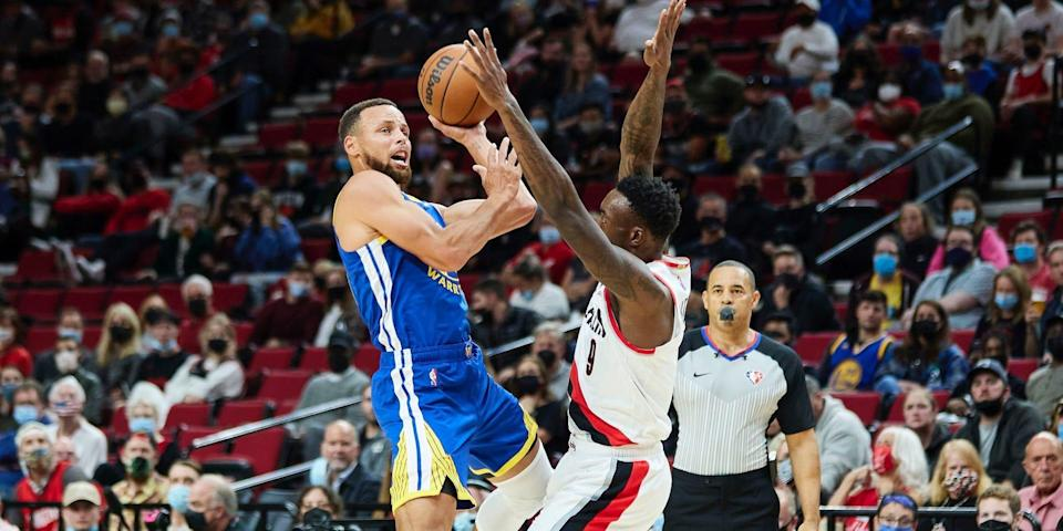 Stephe Curry leans into Nassir Little in an attempt to draw a foul during a preseason game.