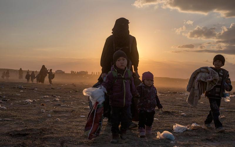 Civilians fleeing from Isil's last remaining territory in Syria arrive at a gathering point before being taken to an internment camp, near Baghuz, in north eastern Syria, on March 6, 2019. - The Telegraph