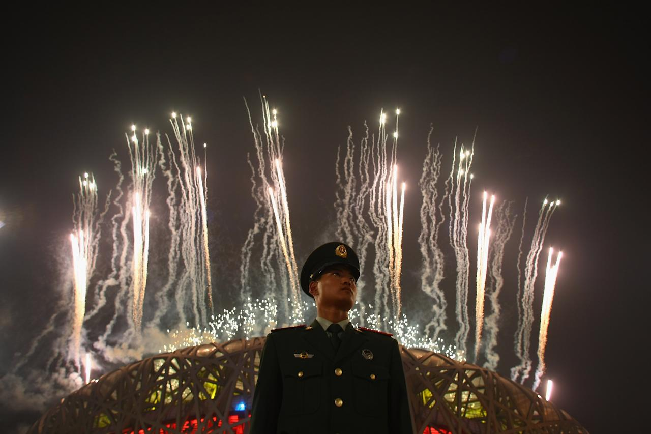BEIJING - AUGUST 24: A Chinese policeman stands guard as fireworks explode over the National Stadium during the Closing Ceremony for the Beijing 2008 Olympic Games on August 24, 2008 in Beijing, China. (Photo by Andrew Wong/Getty Images)