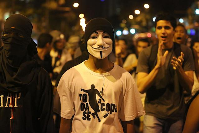 Masked demonstrators protest against the World Cup 2014, in Rio de Janeiro, Brazil, Thursday, March 27, 2014. The demonstrators call for better schools, health care, questioning the billions spent to host this year's World Cup and the 2016 Olympics. (AP Photo/Leo Correa)