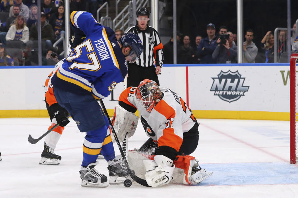 Philadelphia Flyers goalie Brian Elliott (37) makes a save against St. Louis Blues forward David Perron (57) during the second period of an NHL hockey game Wednesday, Jan. 15, 2020 in St. Louis. (AP Photo/Dilip Vishwanat)