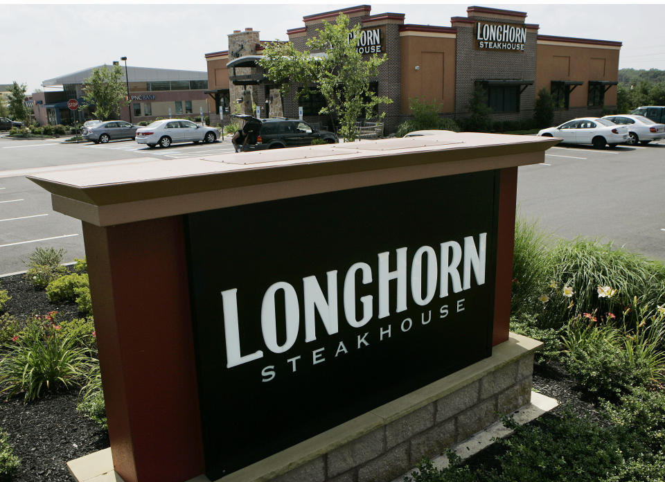 FILE - this July 21, 2008 file photo shows a Longhorn Steakhouse restaurant in Hamilton, N.J. Darden Restaurants says every hourly employee will earn at least $10 per hour including tips starting March 29, 2021. That will rise to $12 per hour in 2023. Orlando, Florida-based Darden, which also owns LongHorn Steakhouse, Cheddar's Scratch Kitchen and others, is also giving one-time bonuses of up to $300 to nearly 90,000 hourly employees. (AP Photo/Mel Evans, File)
