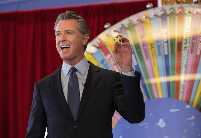 California Gov. Gavin Newsom holds up a lottery ball at the California Lottery Headquarters on Friday, June 4, 2021, in Sacramento, Calif., while drawing numbers for California's new vaccine incentive program. It was the first in a series of drawings for $16.5 million in prize money aimed at encouraging Californians to get their shots ahead of June 15, when the state plans to lift almost all virus-related restrictions. (Paul Kitagaki Jr./The Sacramento Bee via AP)