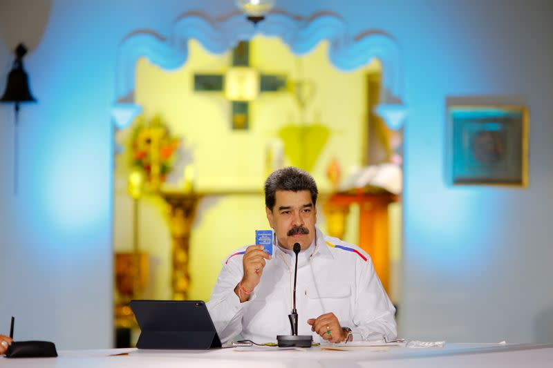 Venezuela's President Nicolas Maduro holds a copy of the Venezuelan constitution during a state television address, in Caracas