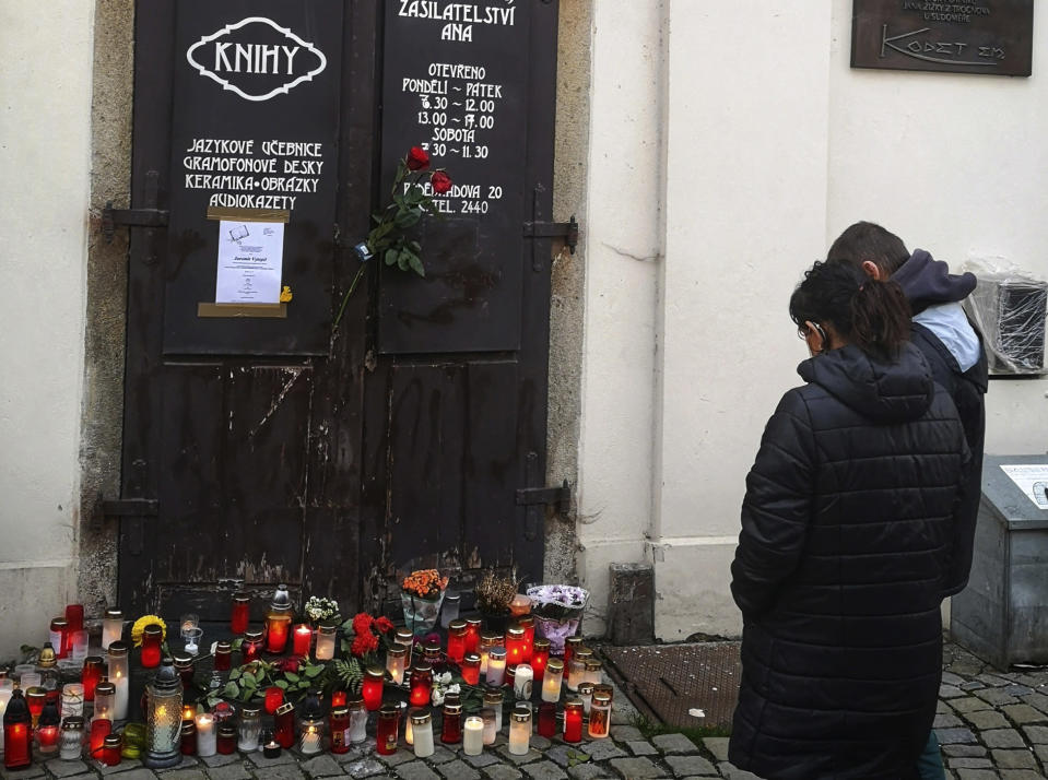 People mourn in front of Jaromir Vytopil's bookstore in Pelhrimov, Czech Republic, Wednesday, Nov. 11, 2020. Some 25,000 have been killed by COVID-19 in the hard-hit Czech Republic. Jaromir Vytopil was one of them. His everyday presence in the small Czech town of Pelhrimov was something everybody took for granted for seven decades as he had served the generations of readers. The longest serving Czech bookseller, passed away on Nov 9. 2020, at age of 83. (AP Photo/Jan Vytopil)