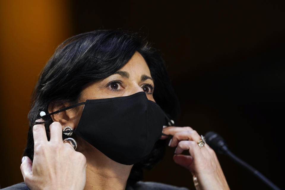 """FILE - Dr. Rochelle Walensky, director of the Centers for Disease Control and Prevention, adjusts her face mask during a Senate Health, Education, Labor and Pensions Committee hearing on the federal coronavirus response on Capitol Hill in Washington, in this Thursday, March 18, 2021, file photo. Walensky says new mask-wearing guidance, coupled with higher rates of vaccination against COVID-19, could halt the current escalation of infections in """"a couple of weeks."""" The director of the Centers for Disease Control and Prevention told """"CBS This Morning"""" she hopes more stringent mask-wearing guidelines and other measures won't be necessary as the country heads into the fall. (AP Photo/Susan Walsh, Pool, File)"""