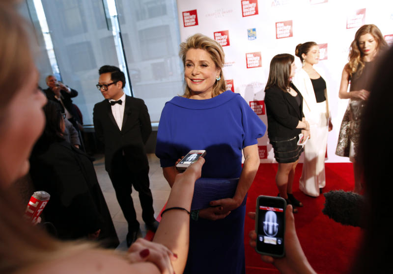 French actress Catherine Deneuve is interviewed as she arrives for the Film Society of Lincoln Center's 39th annual Chaplin Award Gala at Alice Tully Hall, Monday, April 2, 2012 in New York. (AP Photo/Jason DeCrow)