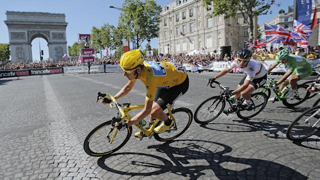 Bradley Wiggins of Britain, wearing the overall leader's yellow jersey is followed by teammate Mark Cavendish of Britain and Peter Sagan of Slovakia, wearing the best sprinter's green jersey as they pass the Arc de Triomphe during the 20th stage of the the Tour de France cycling race over 120 kilometers (74.6 miles) with start in Rambouillet and finish in Paris, France, Sunday July 22, 2012. (AP Photo/Christophe Ena)
