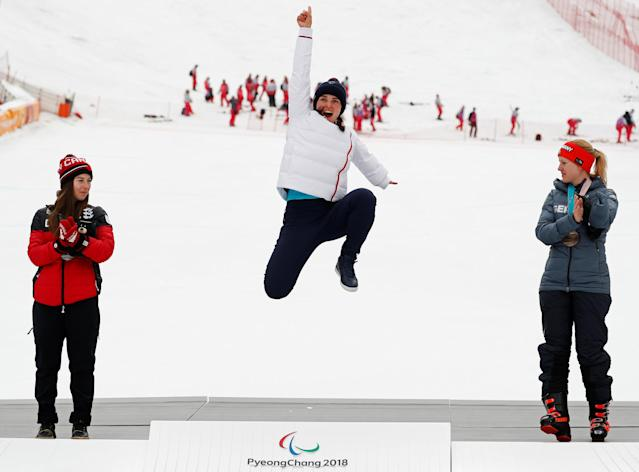 Alpine Skiing - Pyeongchang 2018 Winter Paralympics - Women's Slalom - Standing - Jeongseon Alpine Centre - Jeongseon, South Korea - March 18, 2018 - Gold medallist Marie Bochet of France jumps on the podium as silver medallist Mollie Jepsen of Canada and bronze medallist Andrea Rothfuss of Germany clap. REUTERS/Paul Hanna