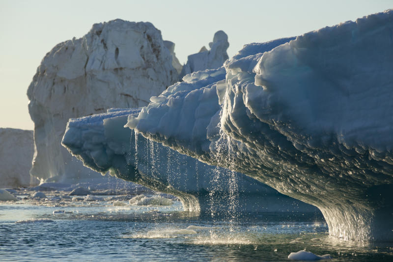 Massive icebergs from Jakobshavn Glacier melting in Disko Bay on sunny summer evening, Ilulissat, Greenland.